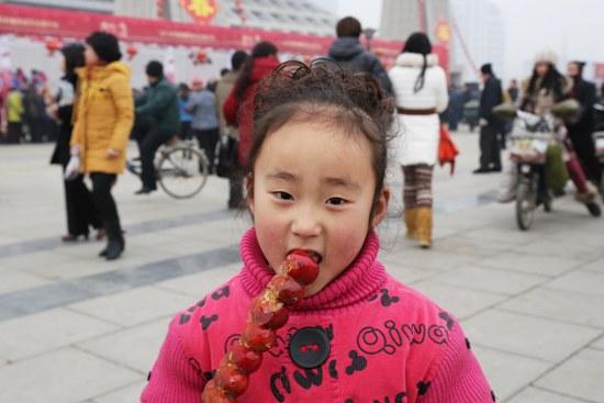 一个名叫雯雯的6岁小女孩口中含着糖葫芦,品尝着蛇年春节的甜蜜.